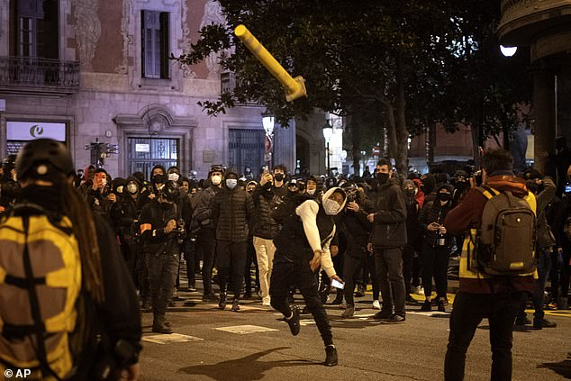 Protests have raged for a sixth night in Barcelona with masked demonstrators throwing bottles, firecrackers and other missiles at police. Pictured: A man throws a bollard at police officers on Sunday
