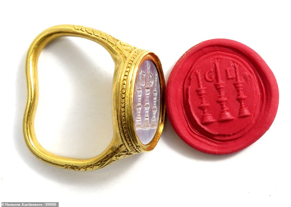 The 400-year-old gold ring is set to fetch £30,000 at auction after being unearthed by a fishmonger. The ring - which is set with a purple-blue Chalcedony gemstone carved with the initials 'GL' and three candles - is set to fetch up to £30,000 on Thursday. Pictured with a red wax imprint