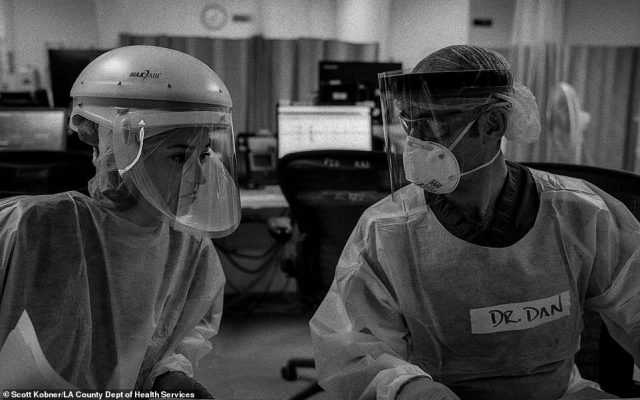 Drs. Katie Ross and Dan Dworkis discuss the care of several patients in the emergency department's COVID-19 unit. The doctors' muffled voices are hard to hear over the sound of air filtration units humming and monitors alarming