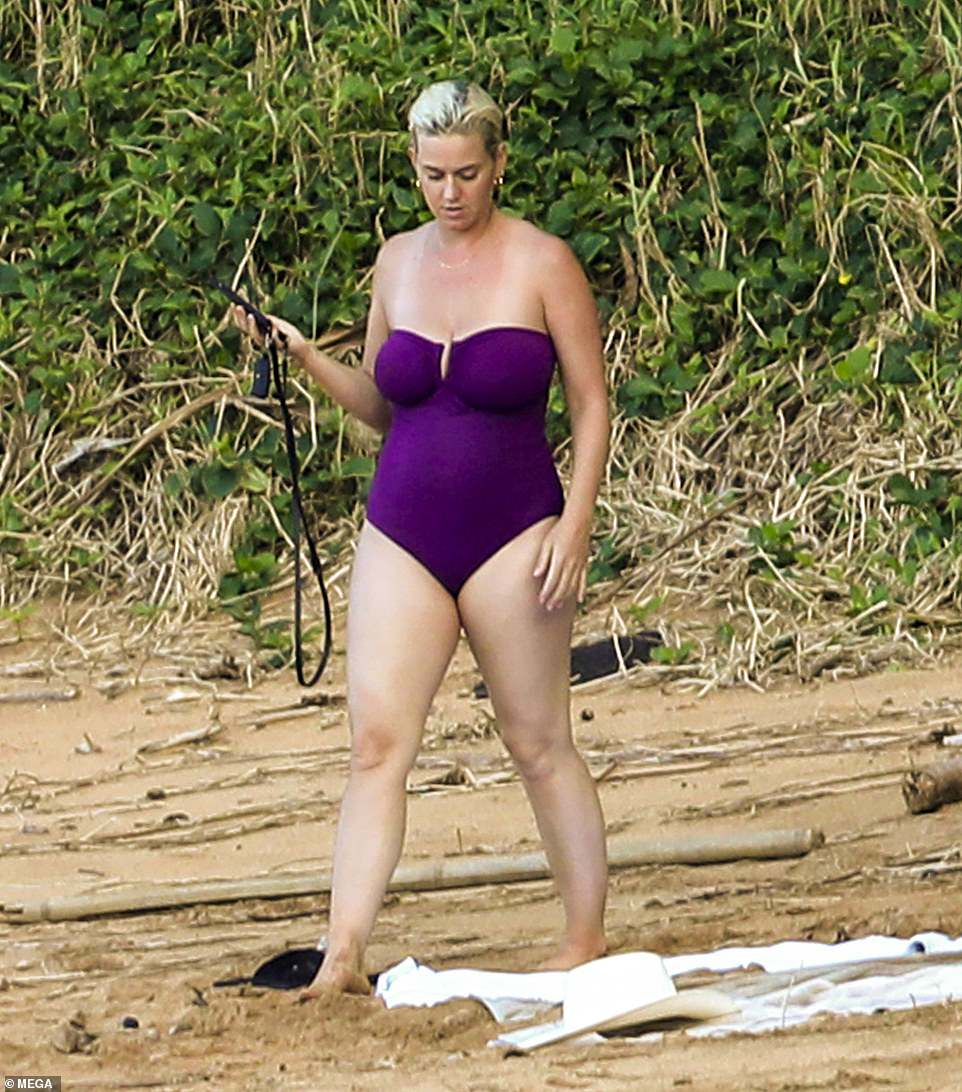 Hot mama! Katy Perry glowed while showing off her fantastic post-pregnancy figure donning a chic strapless purple swimsuit during a winter vacation in Hawaii