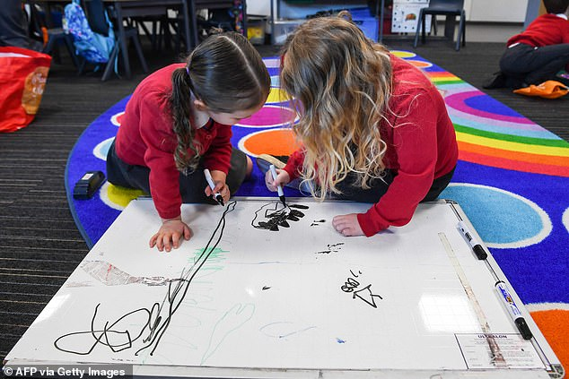 Two pupils draw together on a whiteboard at Clyde Primary School in Glasgow Monday