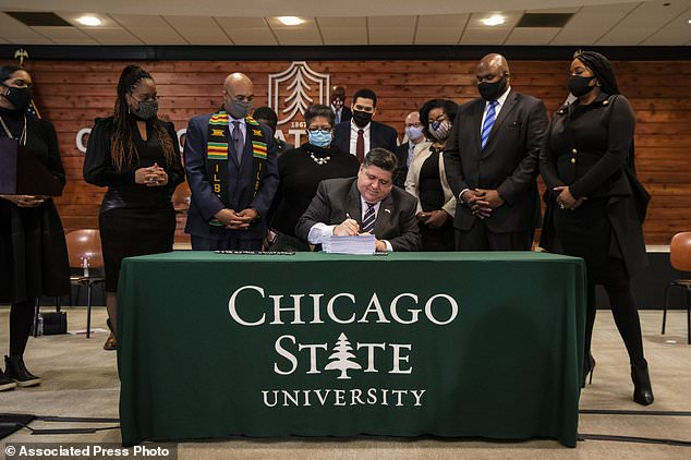 Flanked by lawmakers and supporters, Gov. J.B. Pritzker signs a sweeping criminal justice reform bill into law during a ceremony at Chicago State University on the South Side, Monday, Feb. 22, 2021. (Ashlee Rezin Garcia/Chicago Sun-Times via AP)
