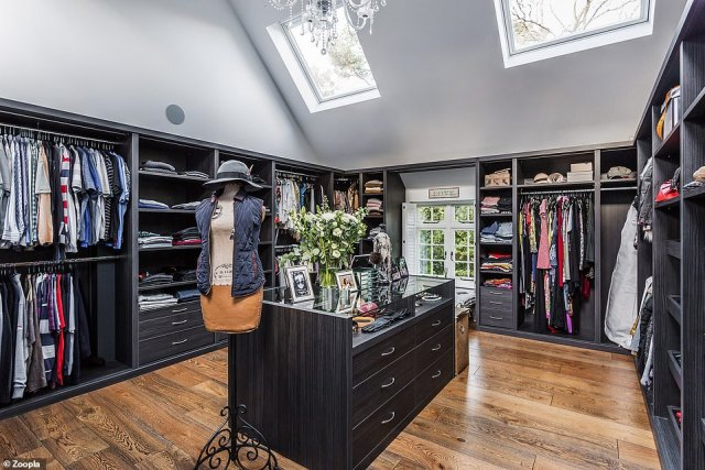 The dressing room in the Farnham property has a vaulted ceiling with dark storage units that contrast with a clear chandelier