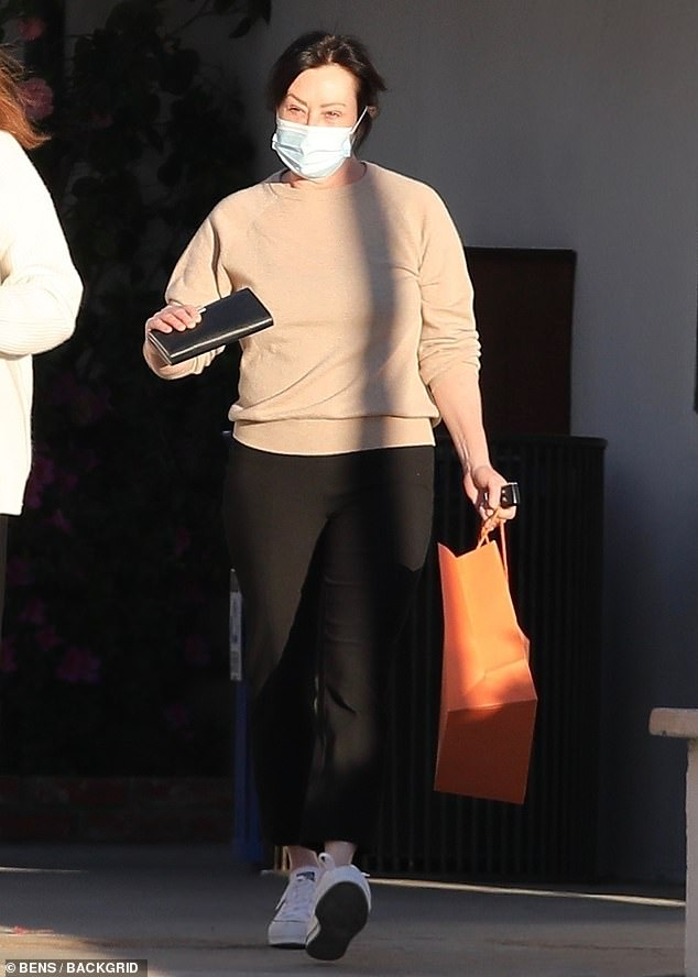 Casual: The Charmed actress, 49, dressed down in a simple camel sweater, black trousers and a blue face covering, completing the casual look with a pair of white Converse trainers