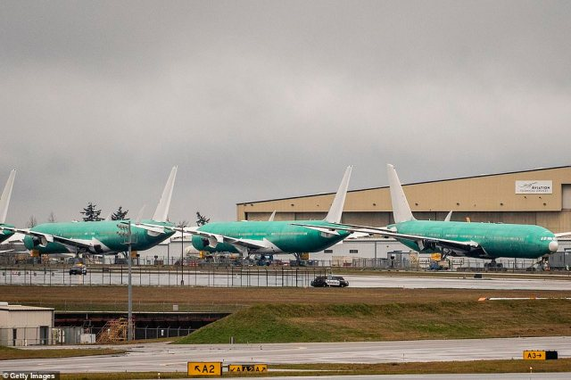 Parked: Boeing 777s stand at a production facility in Everett, Washington on Monday as more than 100 of the aircraft were grounded worldwide because of Saturday's near-calamity in the skies over Denver