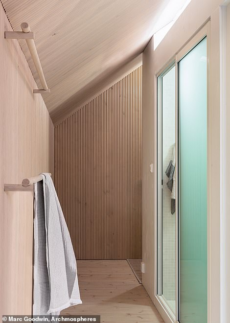 The bathroom, shower and kitchenette are all in a 'rotating core in the middle of the cabin that also houses all tech (ventilation unit, air-source heat pump, water heater, and electrical switchboard)'