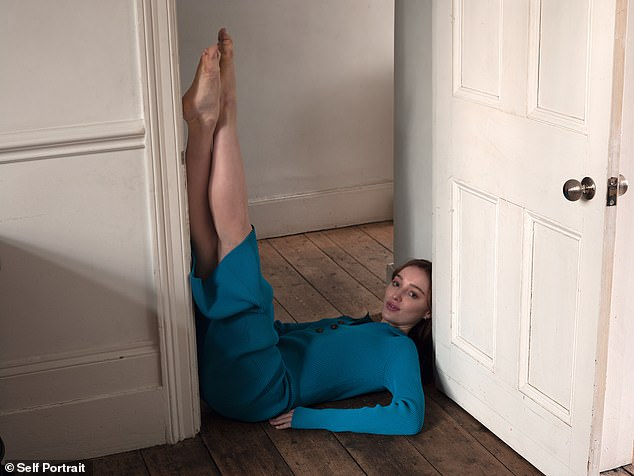 Relaxed: In a separate shot, Phoebe lounged in a doorway with her legs up resting up against the frame, wearing a blue dress with buttons down the front