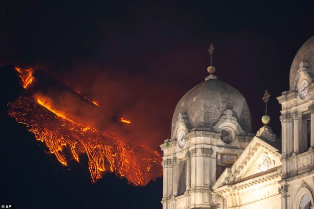 Pictured: Lava flows from the Mt Etna volcano, near Catania in Sicily, southern Italy, Tuesday, Feb. 23 , 2021. The explosion started before midnight on Monday night,with lava visible running behind the domes of the city's Mother Church of Belpasso