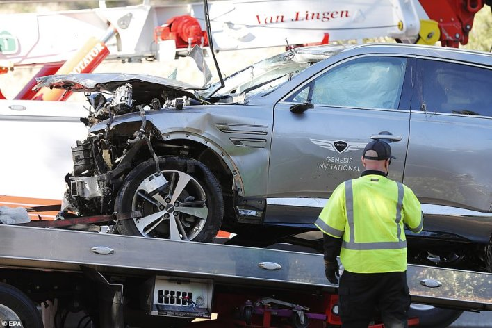 Woods' Genesis SUV is seen being removed from the crash site on Tuesday