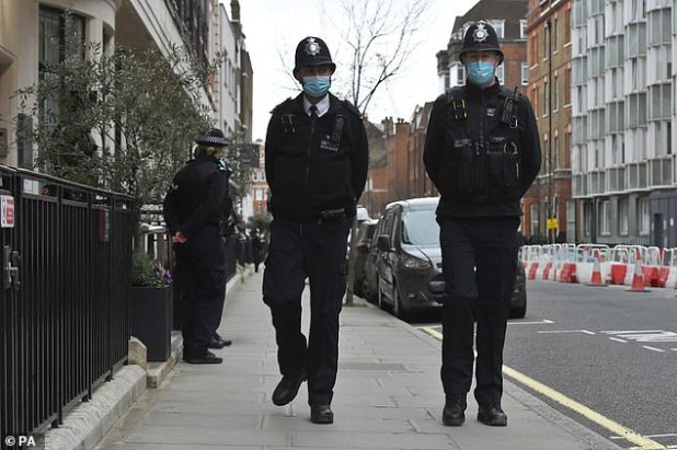 Police officers pass the entrance to King Edward VII Hospital where they admitted Philip