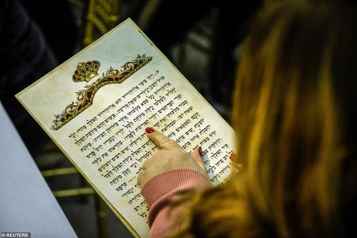 A woman follows along with the reading of the Book of Ester to celebrate the Jewish holiday upon which the festival is based