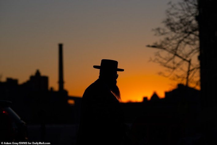 As the sun sets the festival begins. A religious Jewish man's top hat and beard are silhouetted against the dusk sky