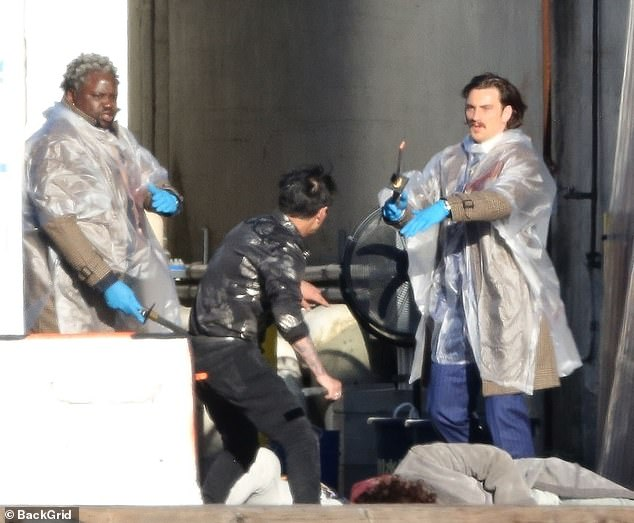 Brutal: Tyree also wore a disposable raincoat and gloves as another bloodied and beaten actor appeared to play dead near Taylor-Johnson's feet