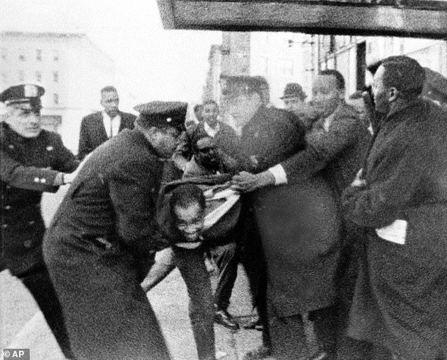 Thomas Hagan, 22, struggles with police who take him from the scene outside the ballroom where Malcolm X was shot and killed