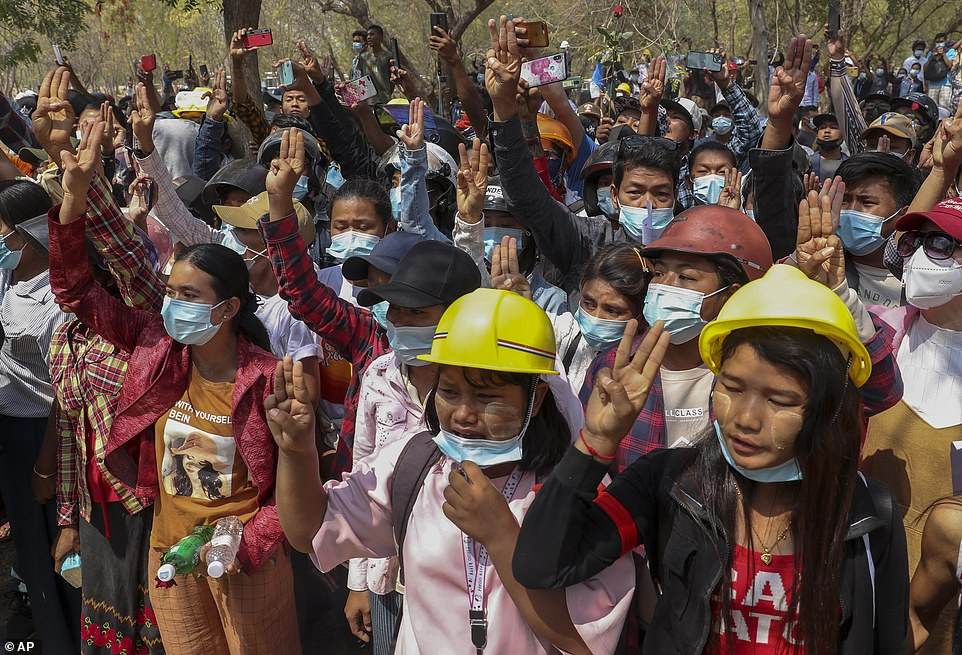 People flash a three-finger sign of resistance during the burial of anti-coup protester Kyal Sin in Mandalay