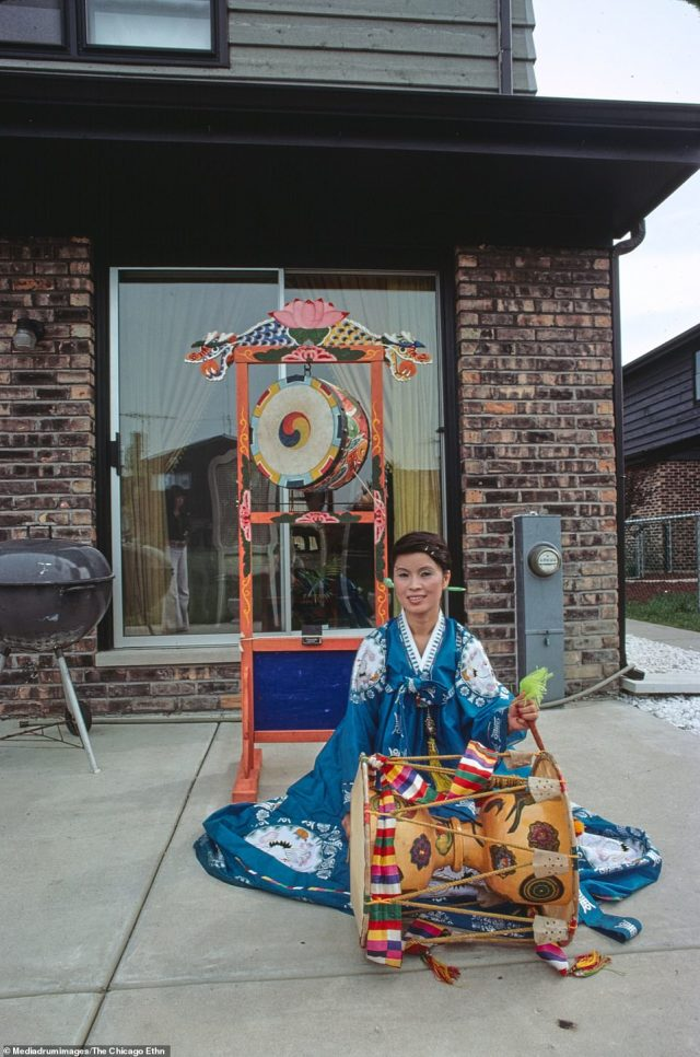 Mrs. Bong Hee (Ma) Stephens, Korean dancer, in her Korean dancing costume with musical instruments, at home