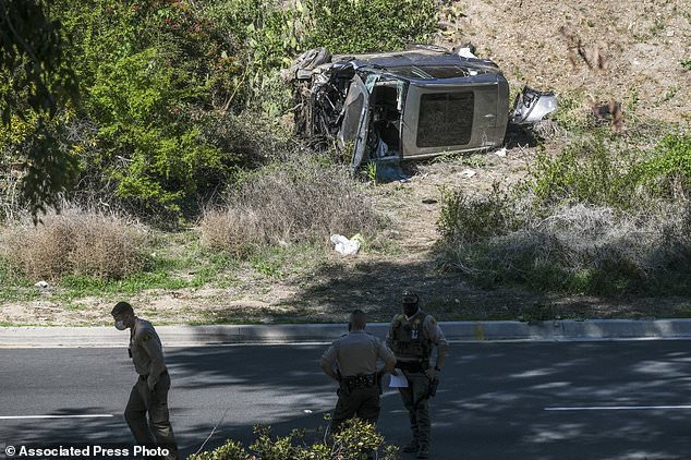 In this Feb. 23, 2021, file photo a vehicle rests on its side after a rollover accident involving golfer Tiger Woods along a road in the Rancho Palos Verdes suburb of Los Angeles