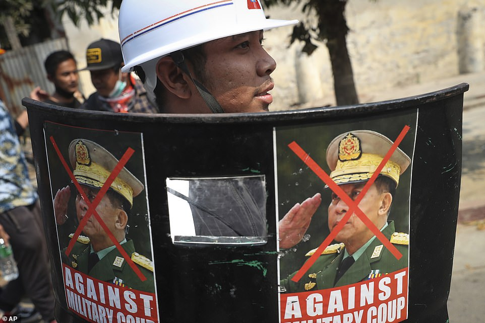 A protester holds a makeshift shield with photos denouncing coup leader Min Aung Hlaing during a demonstration in Mandalay on Saturday