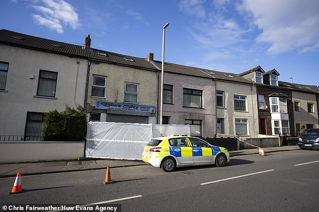 Officers were called to a premises in Baglan Street (pictured this morning), at about midday. Two men have been arrested and are in hospital receiving treatment for serious injuries