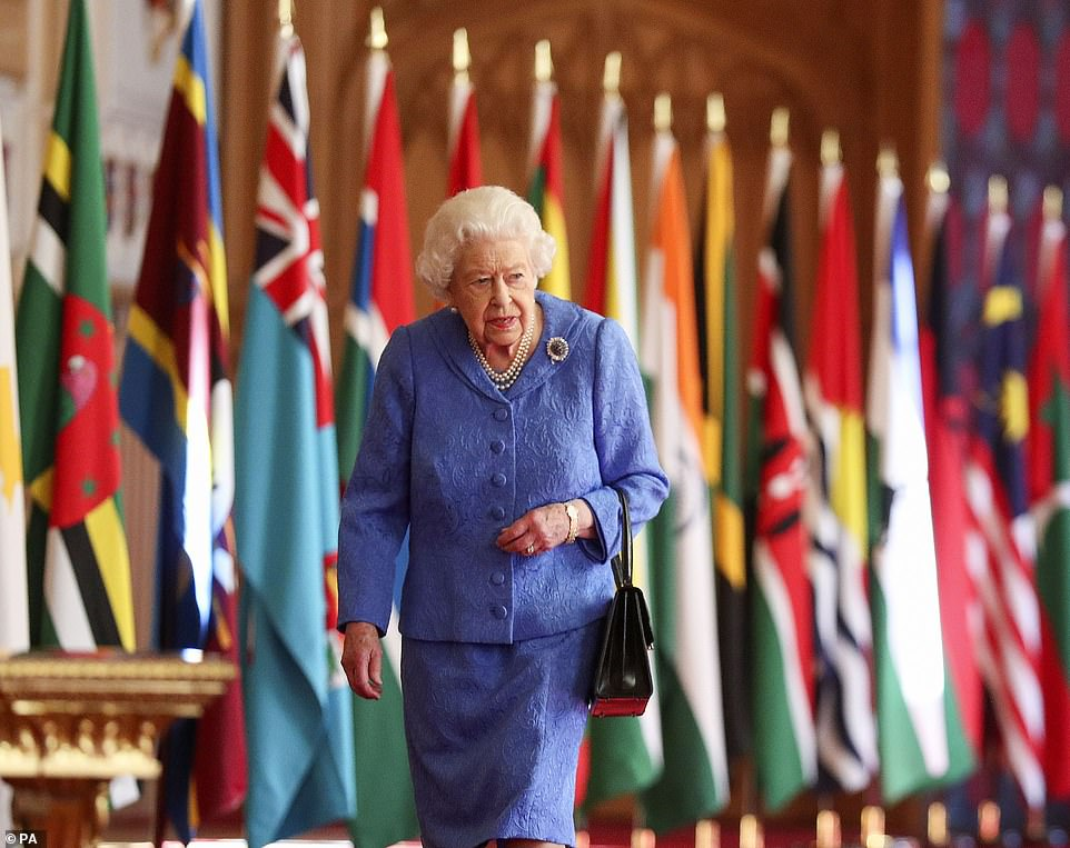 Queen Elizabeth II walks past Commonwealth flags in St George's Hall at Windsor Castle , to mark Commonwealth Day, March 5, 2021