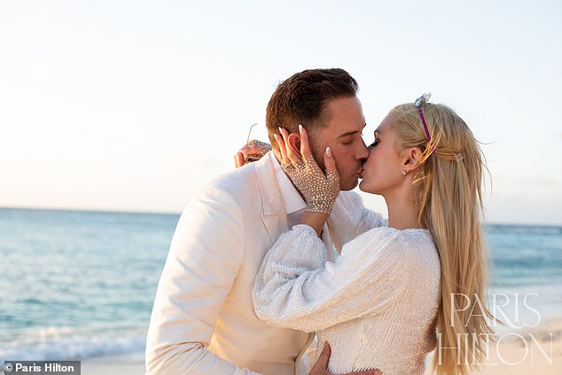 New life: She shared stunning photos of the two dressed in white as the venture capitalist knelt down to ask for Paris' hand in marriage