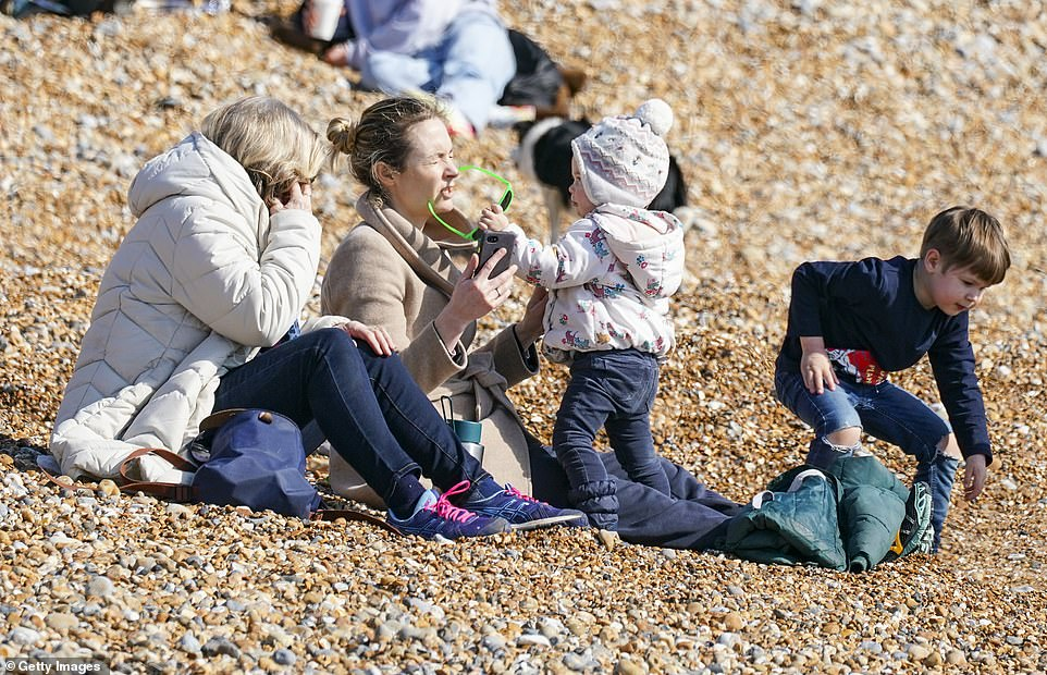 So-called wrap-around childcare will also be allowed to resume, paving the way for after and before school clubs to reopen from tomorrow. Pictured: Two women take advantage of the sunny weather to take their children to the beach earlier today