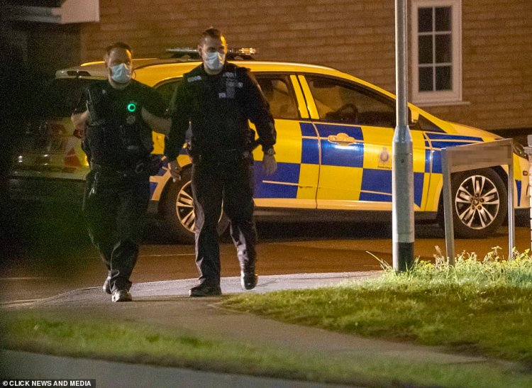 Taking a look: Two police officers were seen looking around Megan's street on Saturday night