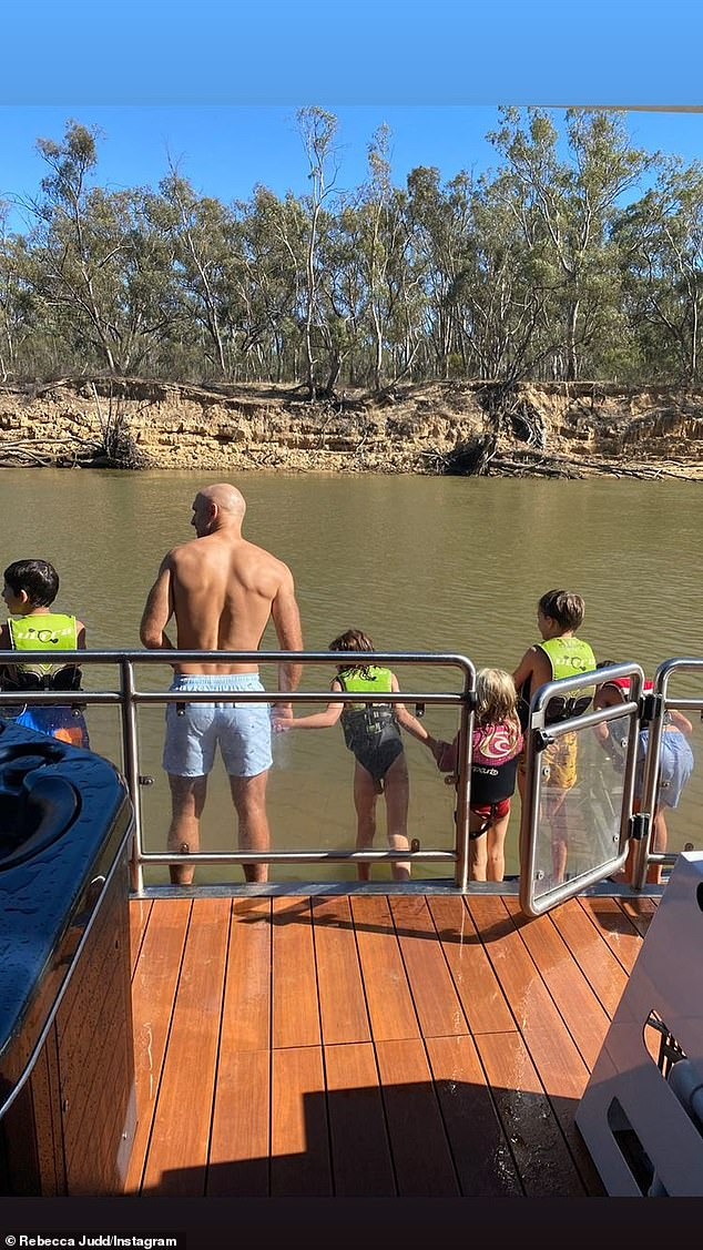 Stay Safe: In yet another image, Chris and the kids wear life jackets as they jump off the edge of their barge into the water