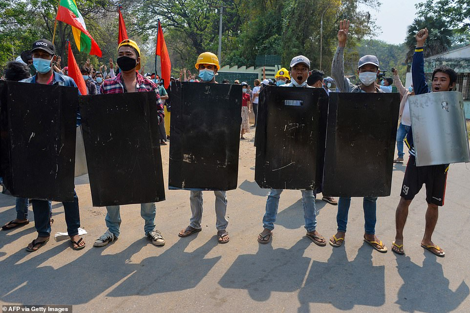 Protesters hold homemade shields as they face off with police during a demonstration against the military coup in Naypyidaw on March 8
