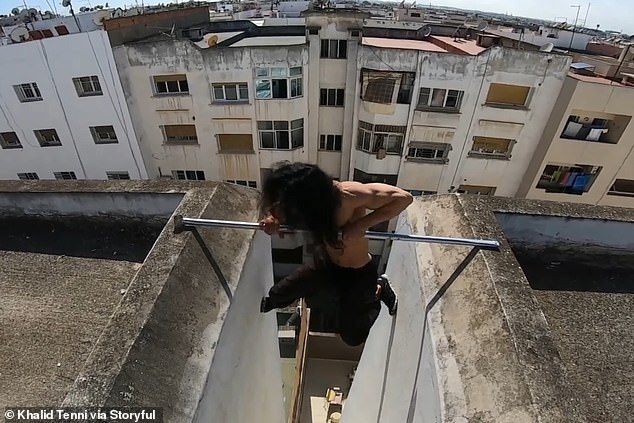 The parkour athlete then proved he has nerves of steel as he shimmied into place and lowered himself down