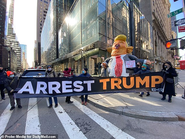 Demonstrators on Fifth Avenue held signs reading 'Arrest Trump' and 'Florida Man Go Home' on Monday morning, after Trump arrived in New York solo on Sunday