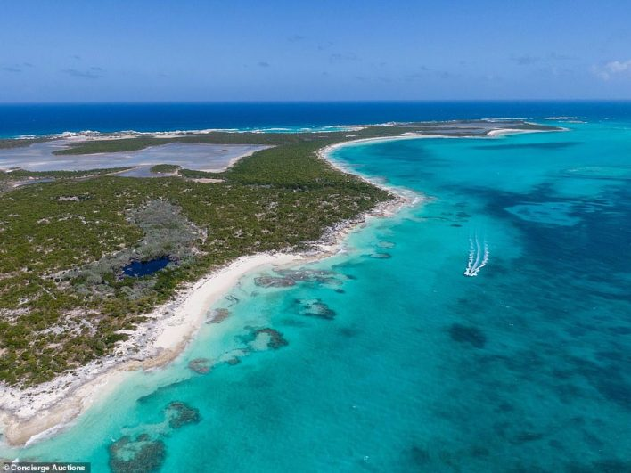 A boat is seen sailing alongside the island, which is set to go up for auction later this month
