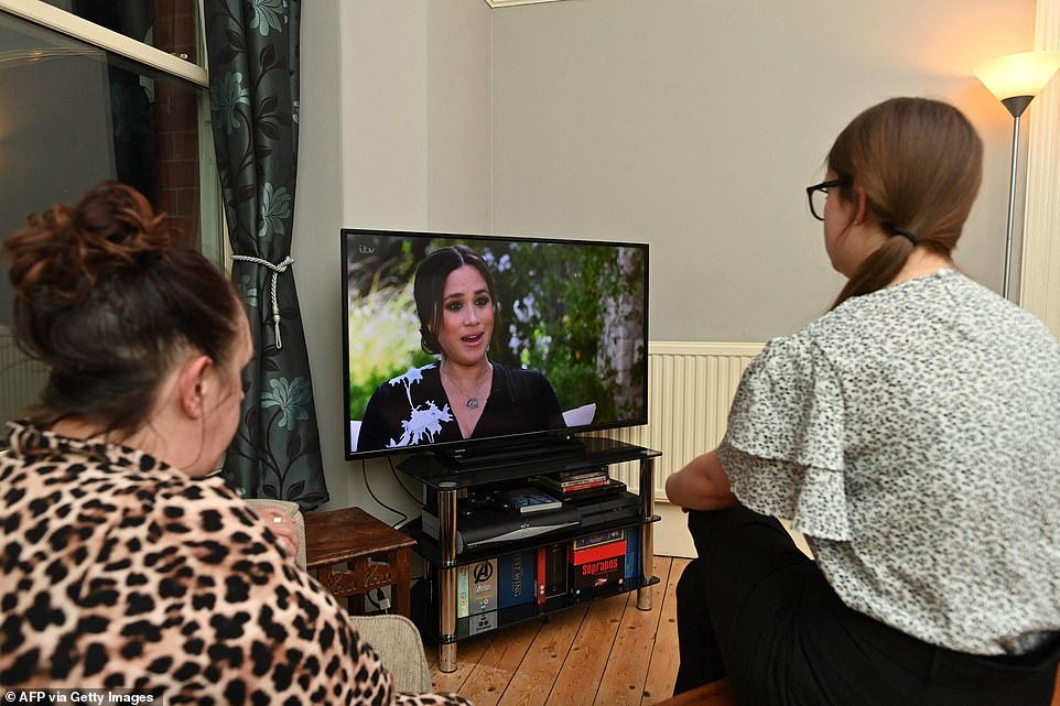 A family gather around the television in Liverpool to watch Prince Harry and his wife Meghan's interview on ITV tonight