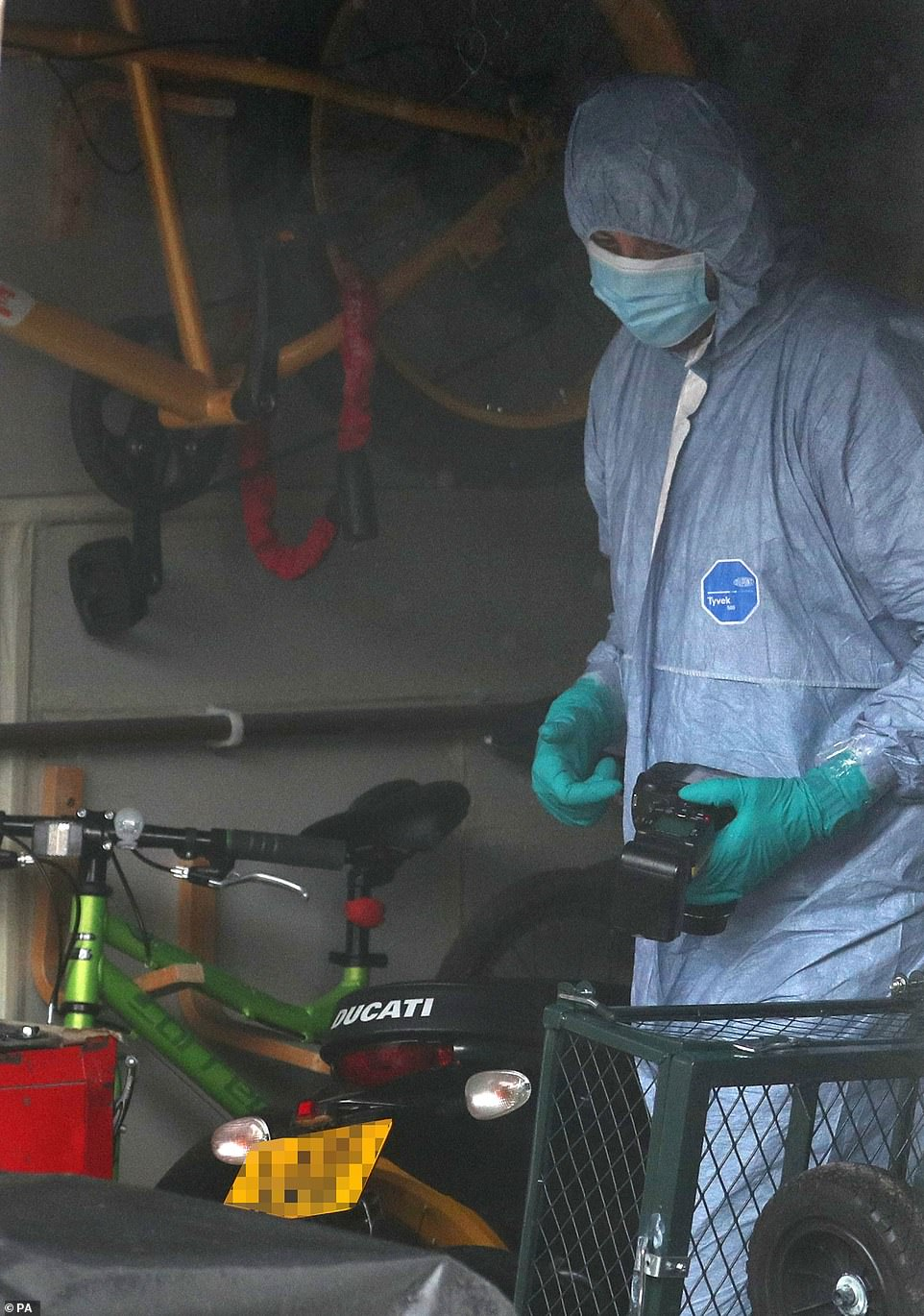 A forensic officer takes pictures inside the garage of the family home of serving police officer Wayne Couzens today