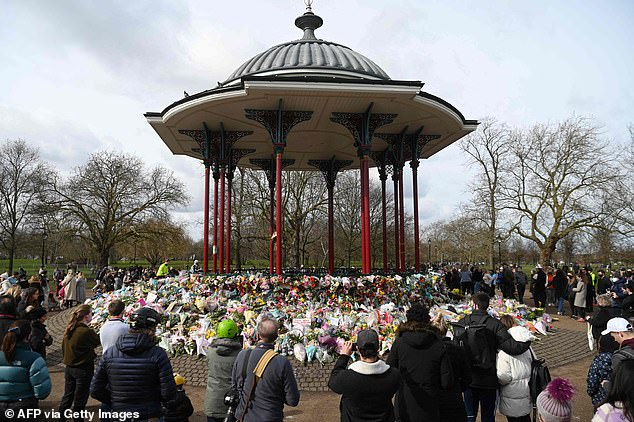 Well-wishers gather beside floral tributes to honour murder victim Sarah Everard at the bandstand on Clapham Common in south London on March 14