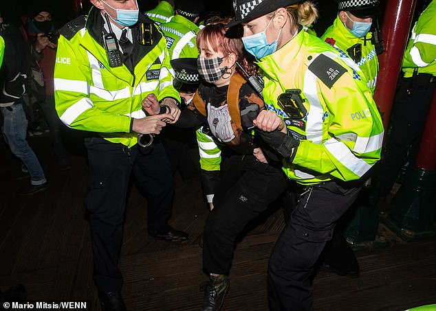 Scuffles broke out as police surrounded a bandstand covered in flowers left in tribute.Pictured: Police arresting a demonstrator