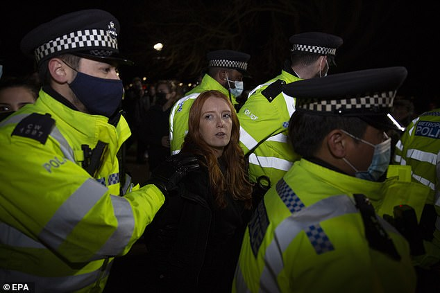 A woman is seen being hauled away by uniformed police officers in Clapham today. She was attending the Sarah Everard vigil