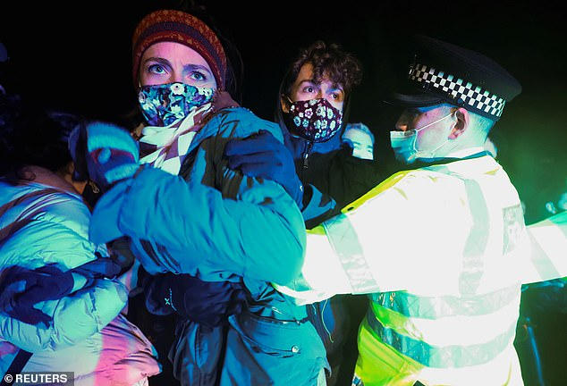 Demonstrators are seen clashing with police officers in Clapham Common last night during a vigil