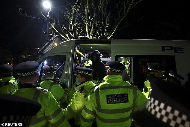 A detained person sits in a police vehicle as people gathered in Clapham last night