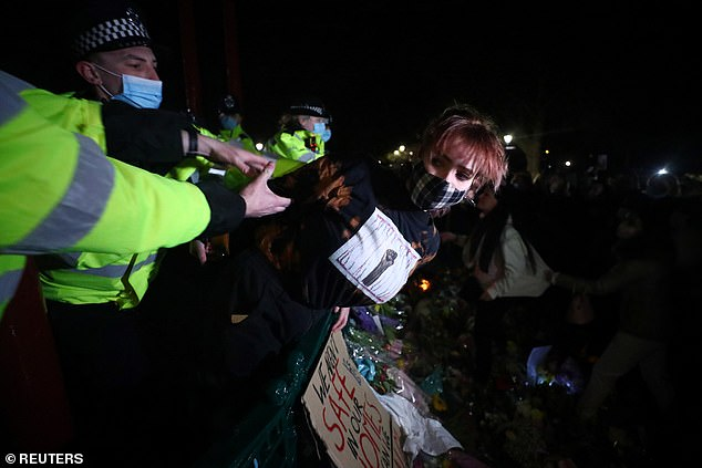 Police detained a woman as people gathered at a memorial site in Clapham Common last night