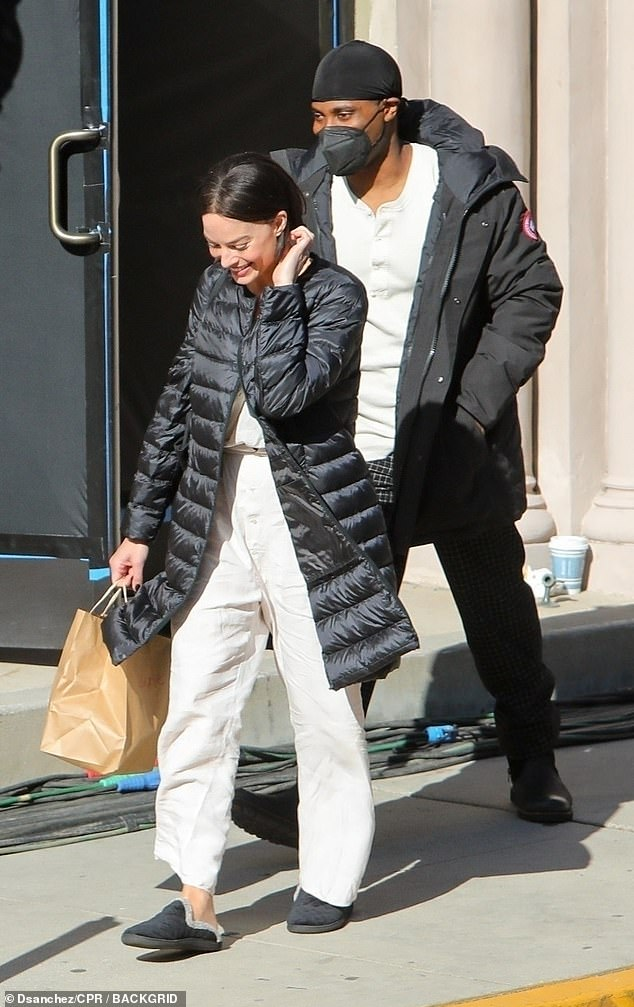 New look: Looking nearly unrecognizable with her new dark hair, the four-time Golden Globe winner sported a long black puffer coat and white linen trousers