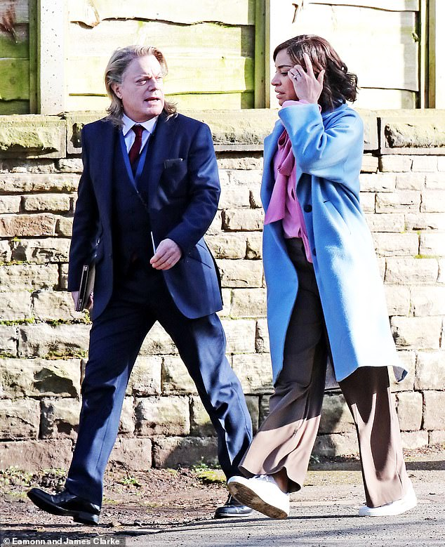 New role: Eddie Izzard transformed into a lawyer named Harry as she was seen filming a new Netflix thriller series in Manchester on Wednesday (pictured with Cush Jumbo)