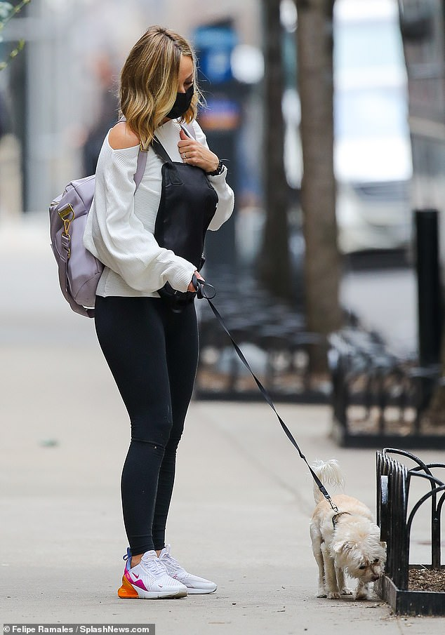 Walk it out: She carried a lavender backpack across her shoulder with a black evolvetogether face mask to match a dog carrier despite her pet pooch walking on a leash