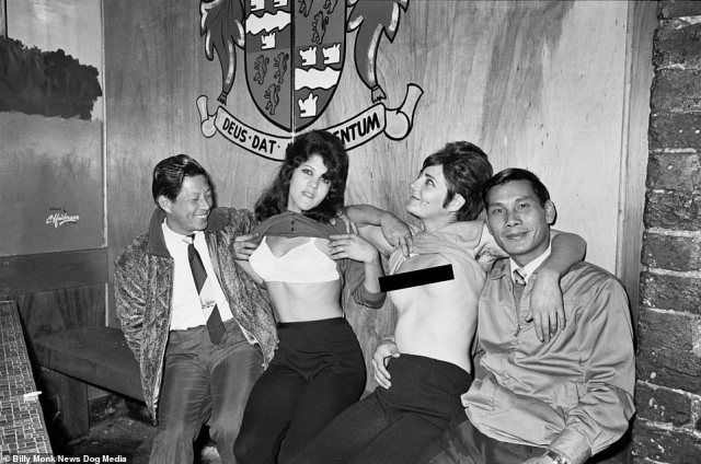 Rare pictures of underground bars in apartheid South Africa have been released marking the anniversary of the referendum that saw the country vote to abolish the system of institutionalised racial segregation. Pictured: Two women flash their breasts as they sit with two men inside The Catacombs bar, Cape Town, South Africa, Wednesday March 12, 1969