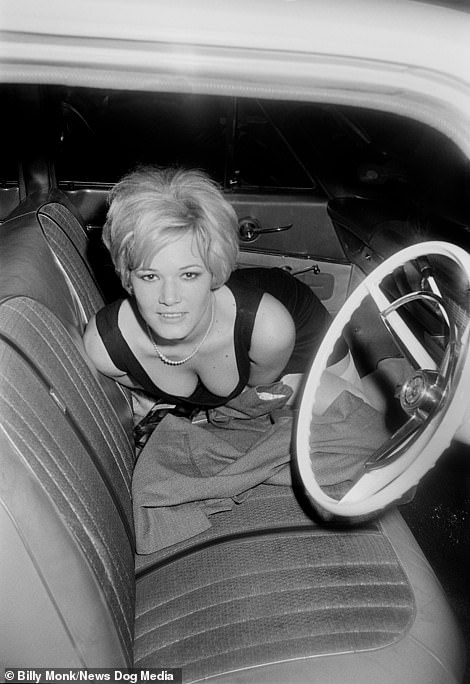 A woman poses inside a car outside The Catacombs bar with a bottle of brandy on the seat, Cape Town, South Africa, Saturday October 14, 1967