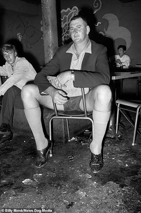 A large man sits on a small chair inside The Catacombs bar, Cape Town, South Africa, Thursday January 25, 1968