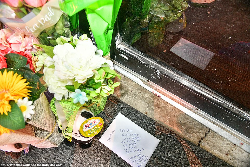 Small droplets of blood can be seen on the ground next to flowers and cards memorializing the victims of the shooting