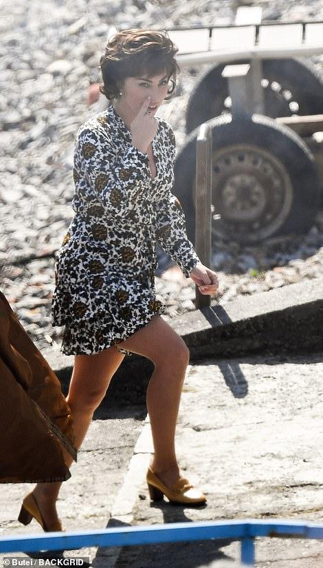 Vestida para matar: la actriz y cantante se transformó en el personaje criminal al usar un vestido blanco ceñido con detalles florales amarillos y negros, combinado con un par de zapatos brogue color crema.