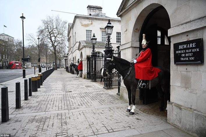 Members of the Household Cavalry stand guard at a nearly-empty Horse Guards in London on March 19, 2020