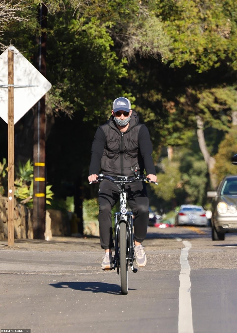 Harry, wearing New Balance trainers, a hooded top, u00A362 Adidas sweatpants, The Mission Continues veterans' association baseball cap, sunglasses and mask, looked serious while racing through LA traffic
